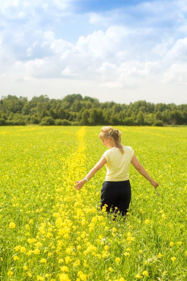 Счастливая молодая женщина наслаждаясь летом и природой в желтом поле цветка с солнечным светом, сработанностью и здоровым образо стоковые изображения
