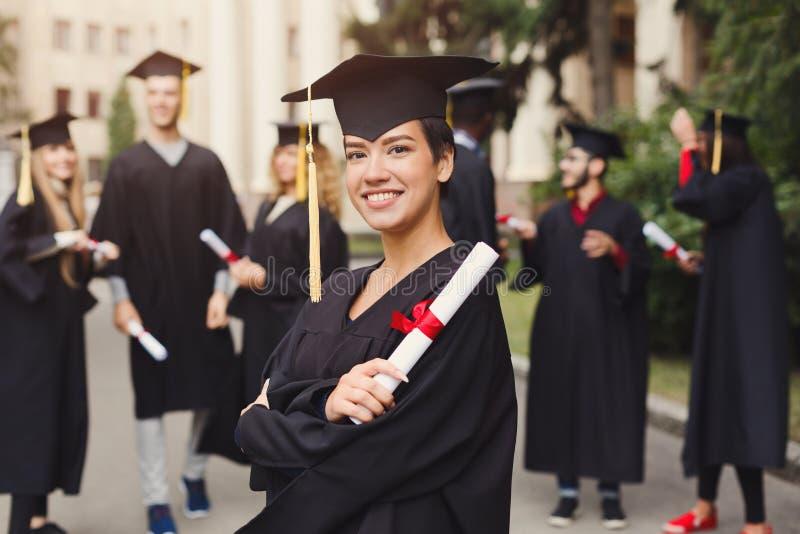 Счастливая молодая женщина на ее выпускном дне стоковая фотография rf