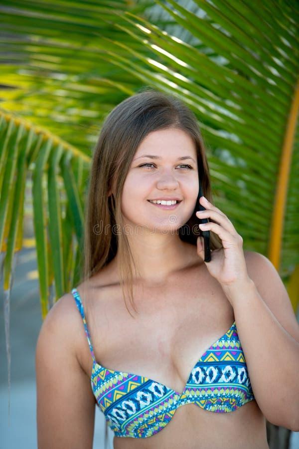 Счастливая молодая женщина под пальмой говоря по умному телефону стоковые фото