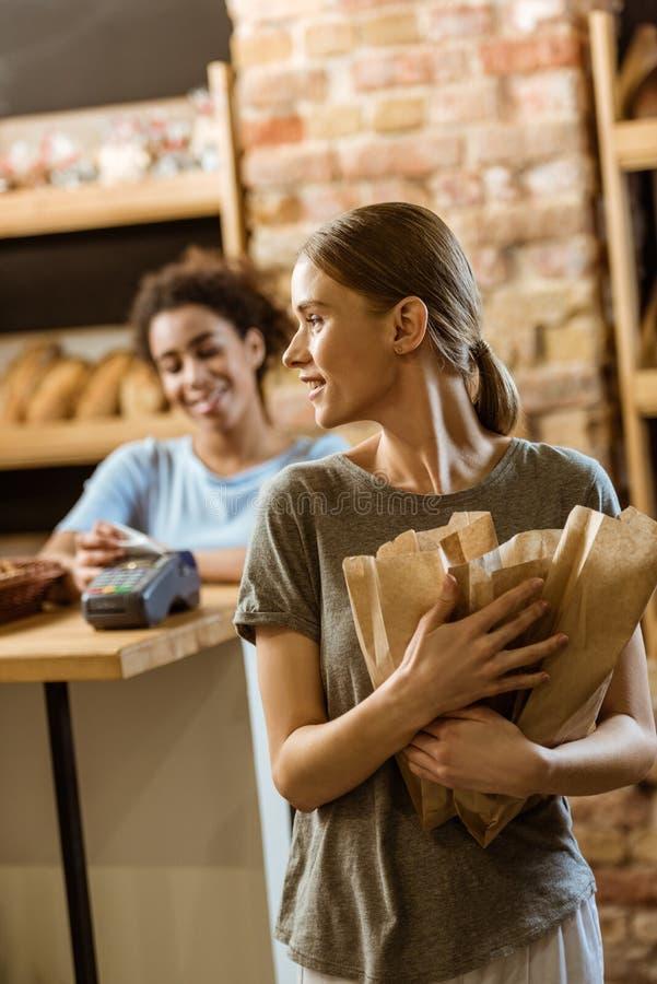 счастливая молодая женщина покидая магазин печенья с различным хлебом стоковое фото rf