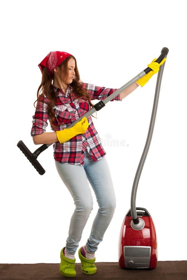 Счастливая молодая женщина поя по мере того как она очищает с пылесосом стоковые изображения
