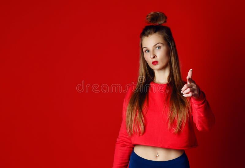 Счастливая молодая женщина пригодности показывая большие пальцы руки вверх стоковое изображение
