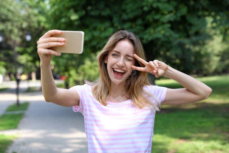 Счастливая молодая женщина принимая selfie стоковое фото