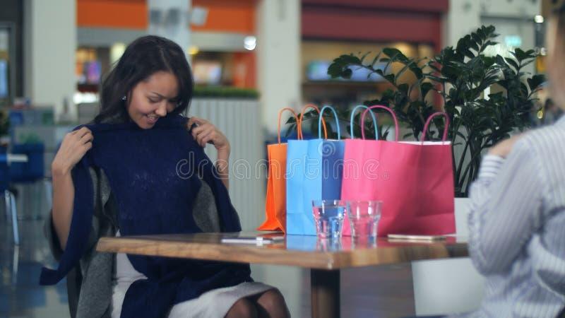 Счастливая молодая женщина при хозяйственные сумки показывая новые одежды к ее другу стоковые фото