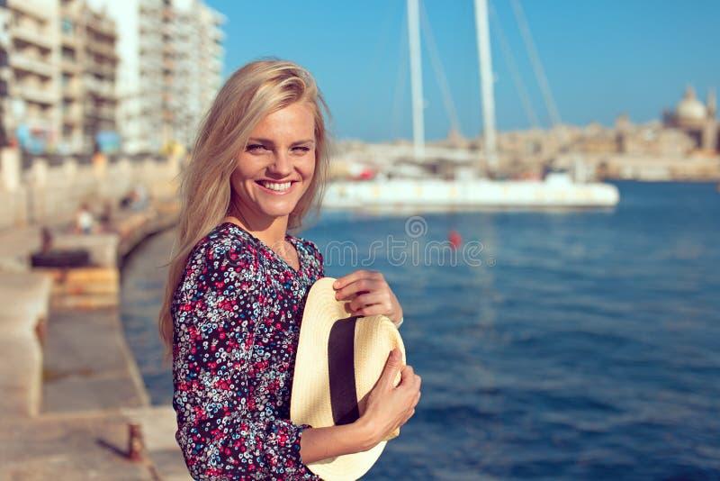 Счастливая молодая женщина путешественника на море смотря к камере стоковые фото