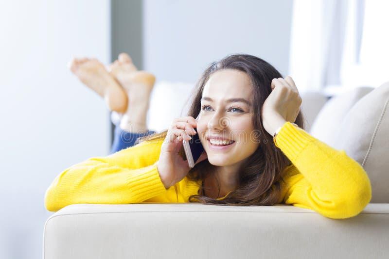 Счастливая молодая женщина разговаривает по телефону стоковые изображения
