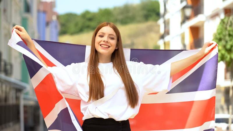 Счастливая молодая женщина, размахивая британским флагом и улыбаясь на камеру, патриотизм, праздник стоковые изображения rf