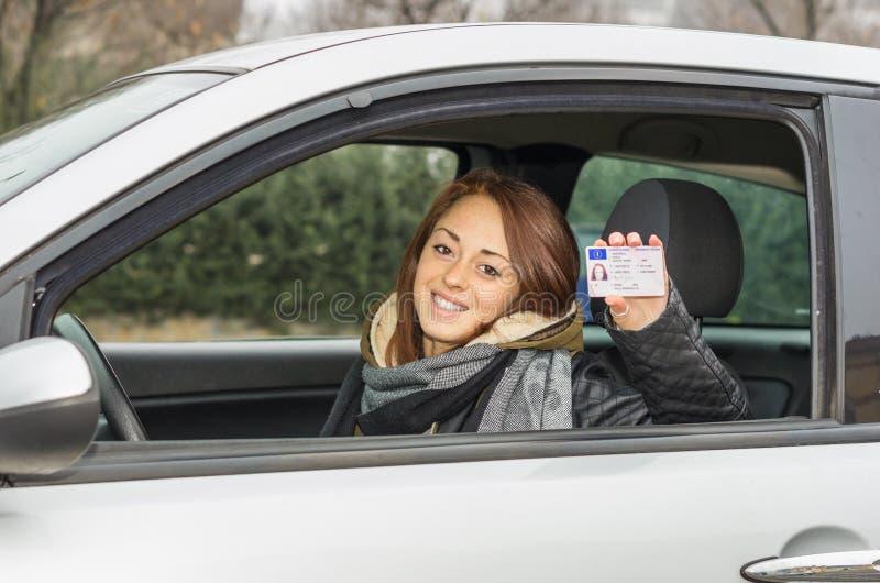 Счастливая молодая женщина сидя в автомобиле усмехаясь на камере показывая ее водительские права стоковое фото rf