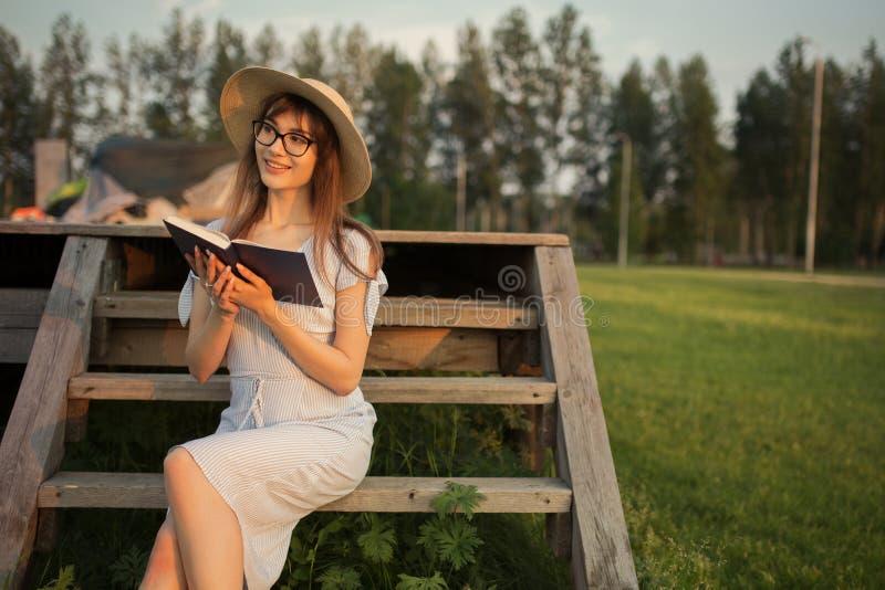 Счастливая молодая женщина сидя в парке Усмехающся и держащ книгу в его руках Сидеть на деревянной скамье Свет захода солнца стоковое изображение rf