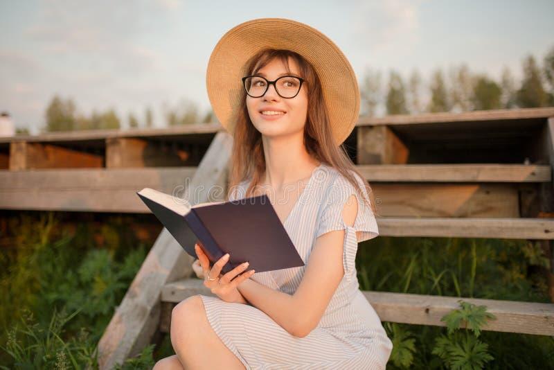 Счастливая молодая женщина сидя в парке Усмехающся и держащ книгу в его руках Сидеть на деревянной скамье Свет захода солнца стоковая фотография rf