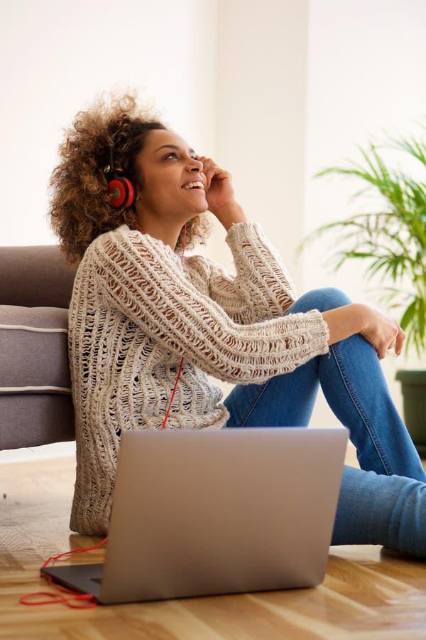 Счастливая молодая женщина сидя дома слушать к музыке с наушниками и компьтер-книжкой стоковые изображения