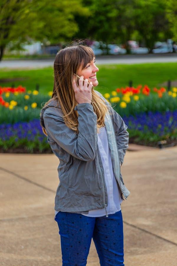 Счастливая молодая женщина слушая ее телефон в парке стоковые фотографии rf