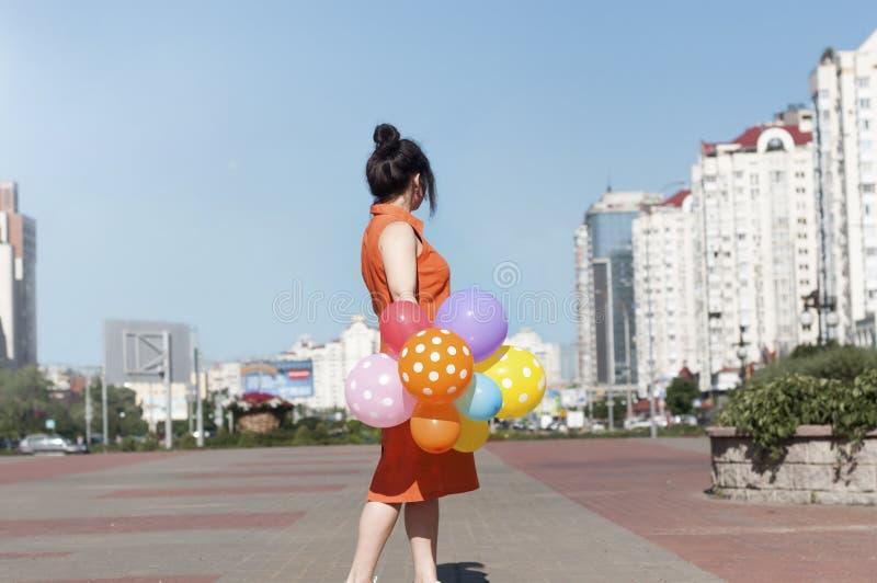Счастливая молодая женщина с воздушными шарами на городской площади стоковые фотографии rf