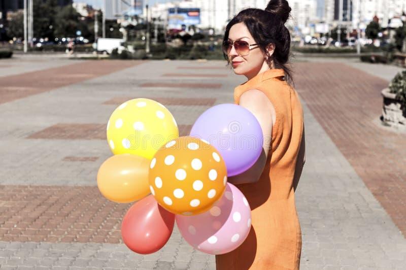 Счастливая молодая женщина с воздушными шарами на городской площади стоковые изображения rf