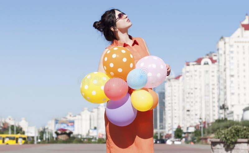 Счастливая молодая женщина с воздушными шарами на городской площади стоковая фотография