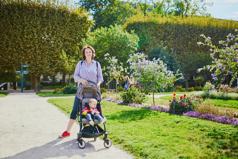 Счастливая молодая женщина с ее маленьким ребенком в прогулочной коляске стоковое изображение