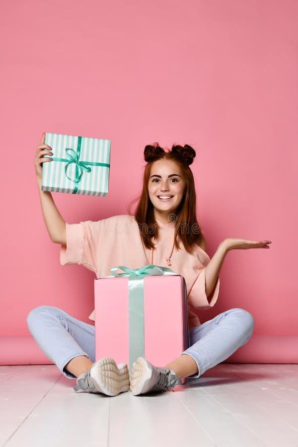 Счастливая молодая женщина с подарками над розовой предпосылкой стоковая фотография