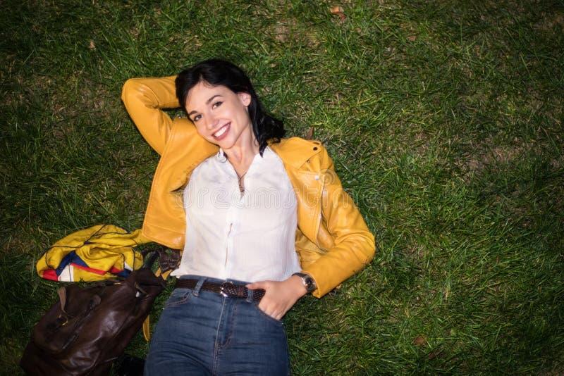 Счастливая молодая женщина усмехаясь и лежа на зеленой траве нося красочное обмундирование с желтой курткой и голубыми джинсами в стоковые изображения