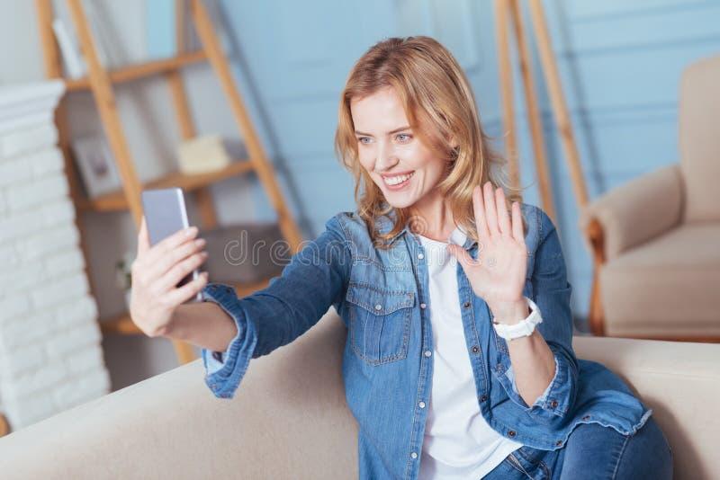 Счастливая молодая женщина усмехаясь пока имеющ видео- звонок с другом стоковая фотография rf