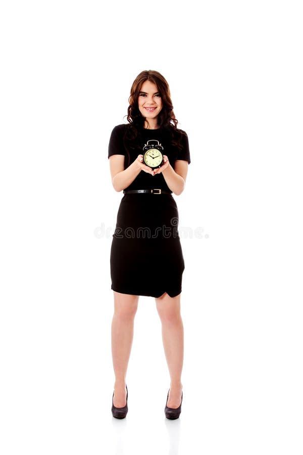 Счастливая молодая коммерсантка держа будильник стоковое изображение rf