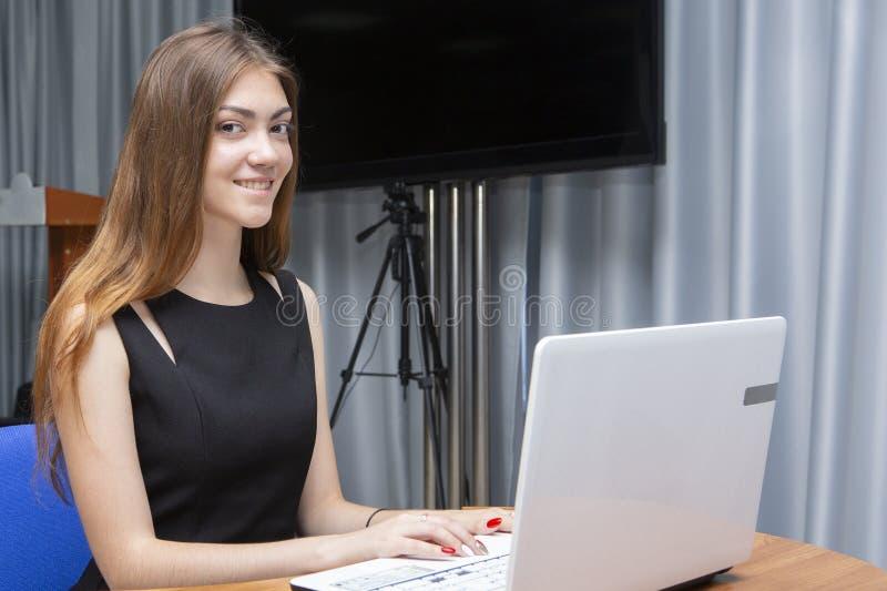 Счастливая молодая красивая женщина используя ноутбук, внутри помещения стоковая фотография