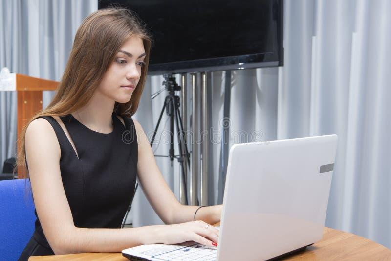 Счастливая молодая красивая женщина используя ноутбук, внутри помещения стоковая фотография rf