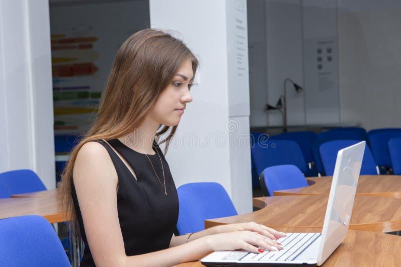 Счастливая молодая красивая женщина используя ноутбук, внутри помещения стоковые фотографии rf