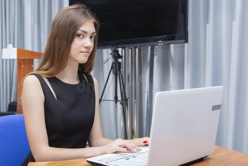 Счастливая молодая красивая женщина используя ноутбук, внутри помещения стоковое фото rf