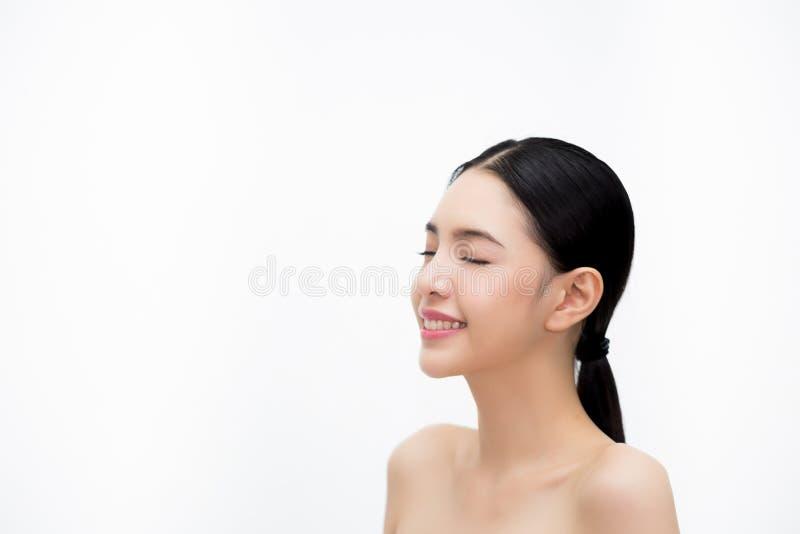 Счастливая молодая красивая и элегантная азиатская женщина в взгляде со стороны изолированная над белыми предпосылкой, концепцией стоковое изображение rf