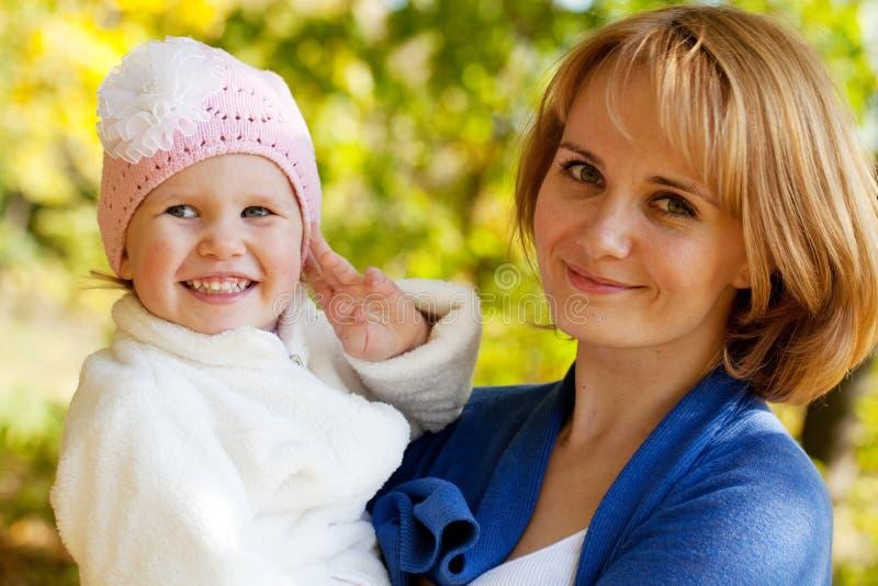 Счастливая молодая мать держа его дочь стоковое изображение rf