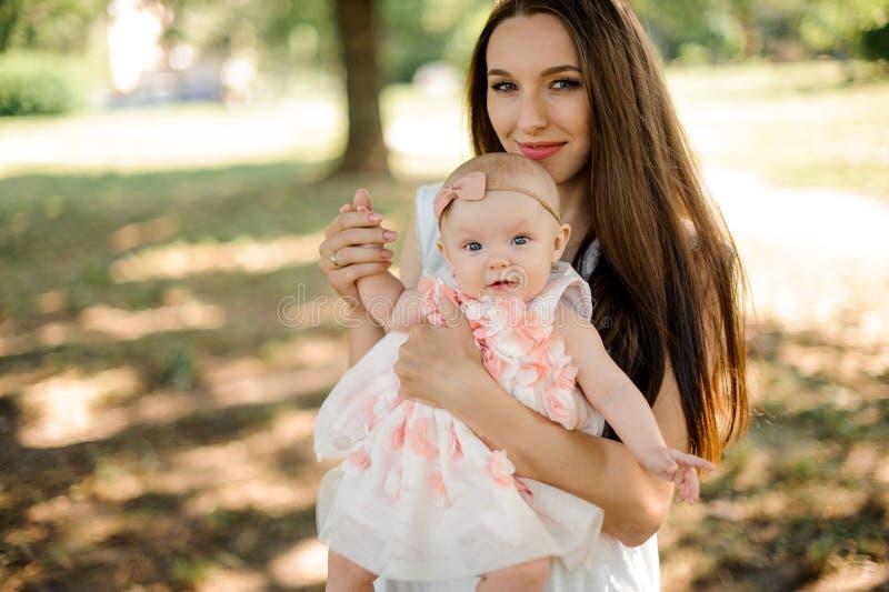 Счастливая молодая мать идя с милым ребёнком в парке стоковые фотографии rf