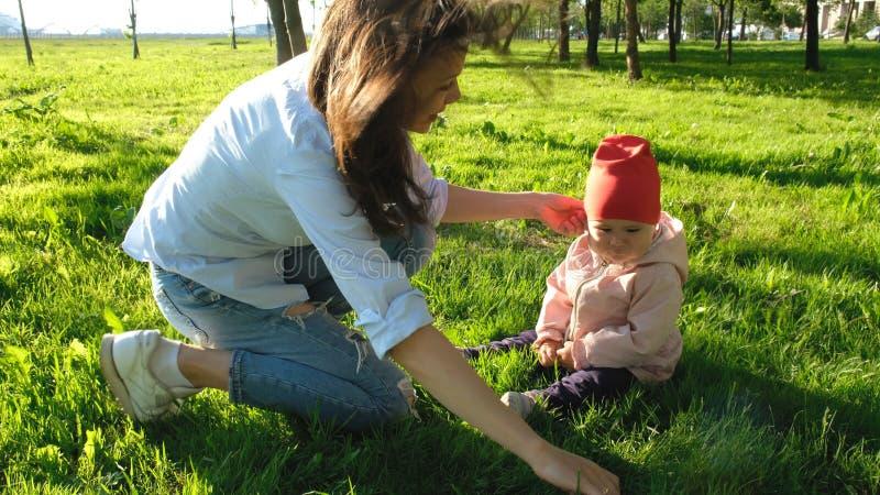 Счастливая молодая мать при ее ребенок играя с хворостиной в парке на траве стоковые фотографии rf