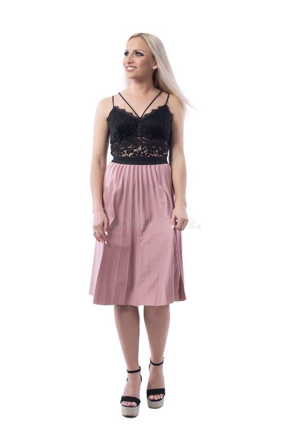 Счастливая молодая милая белокурая женщина в длинной плиссированной юбке идя и смотря вверх стоковое фото