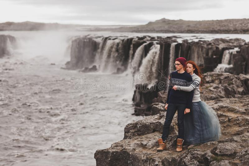 Счастливая молодая пара, влюбленная, гуляла рядом с популярным водопадом Сэлфосс в Исландии стоковое изображение rf