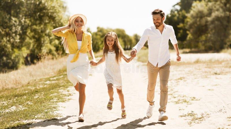 Счастливая молодая семья бежать в сельской местности, панораме стоковое фото rf