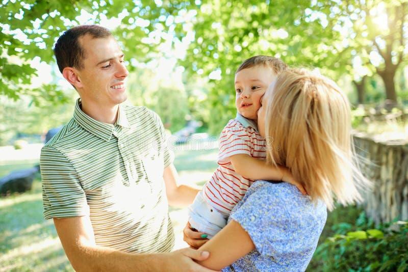 Счастливая молодая семья идя в парк лета Отец матери и освещенный стоковые изображения rf