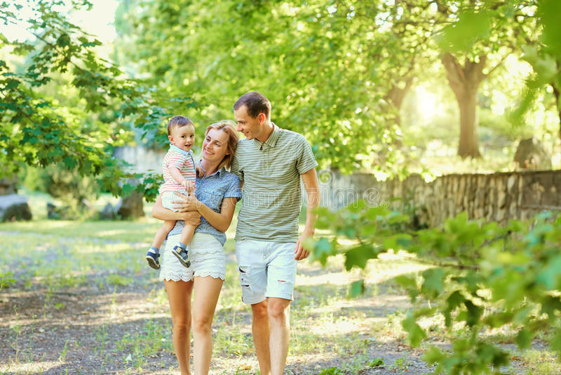 Счастливая молодая семья идя в парк лета стоковое изображение rf
