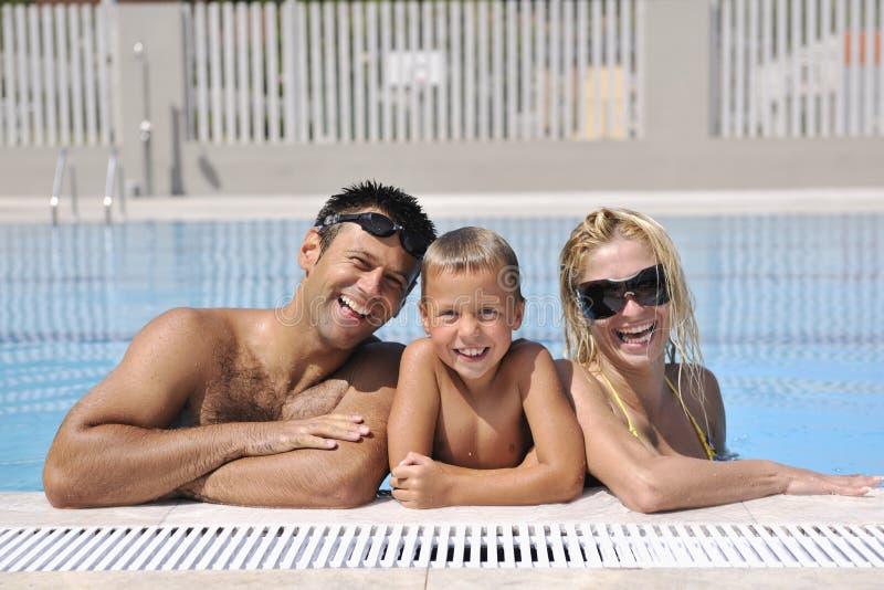 Счастливая молодая семья имеет потеху на плавательном бассеине стоковая фотография