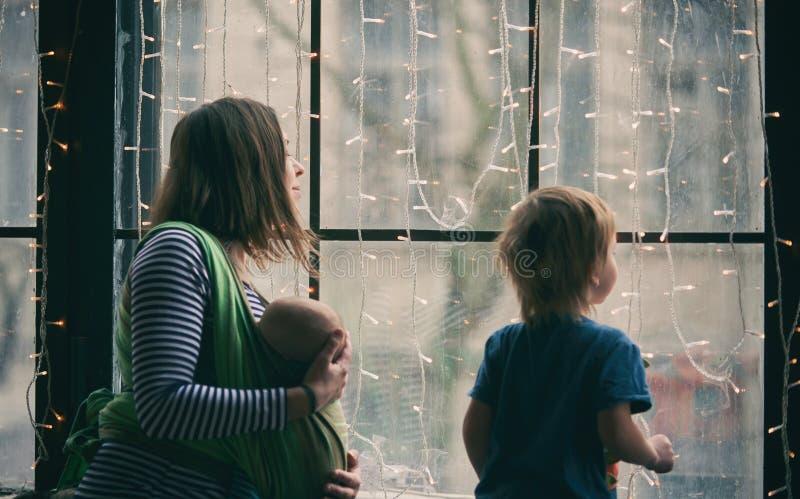 Счастливая молодая семья, красивая мать с 2 детьми, прелестный мальчик preschool и младенец в слинге смотрят совместно через окно стоковые изображения rf
