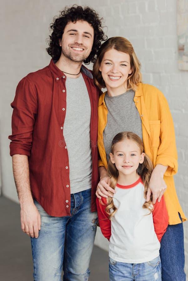 счастливая молодая семья стоя совместно и усмехаясь стоковая фотография rf