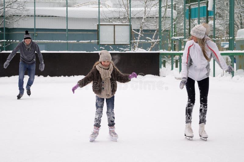 Счастливая молодая семья с коньком ребенка на на открытом воздухе катке в зиме Красивая семья идя и играя на льде внутри стоковые фото