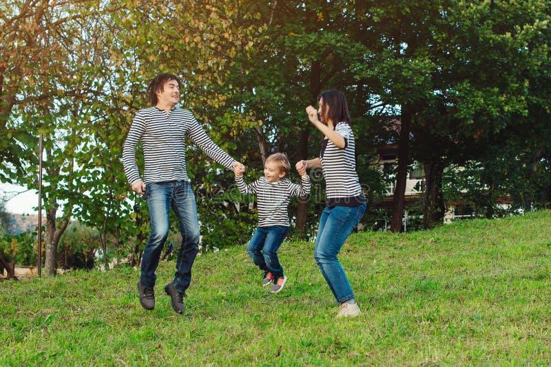 Счастливая молодая семья тратя время совместно в парке стоковая фотография rf