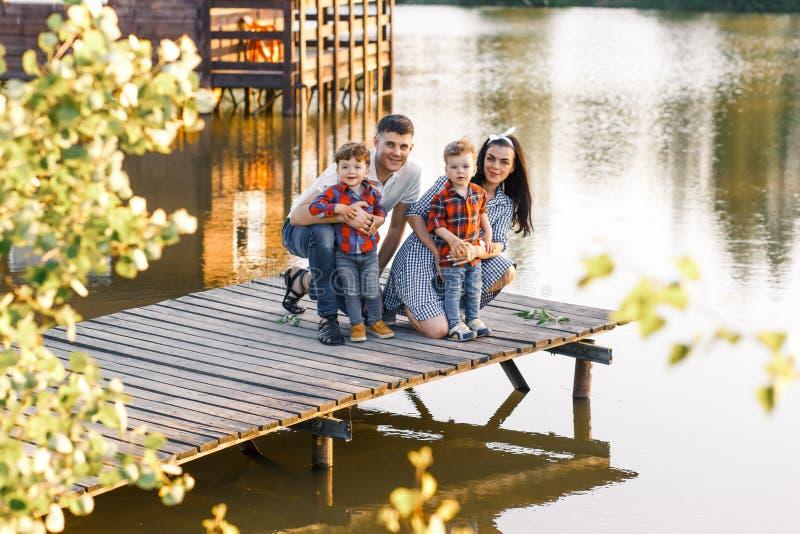 Счастливая молодая семья тратя время совместно снаружи в зеленой природе Родители играя с близнецами снаружи стоковое изображение rf