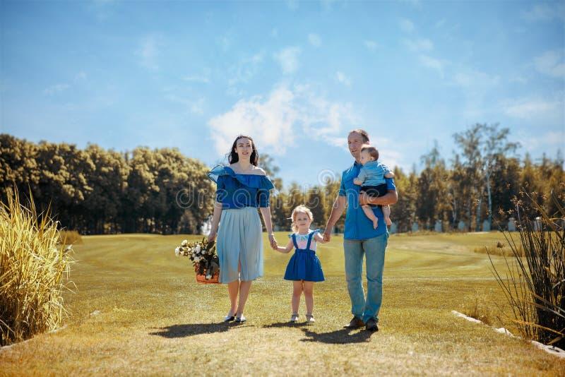 Счастливая молодая семья тратя время совместно снаружи в зеленой природе стоковое изображение rf
