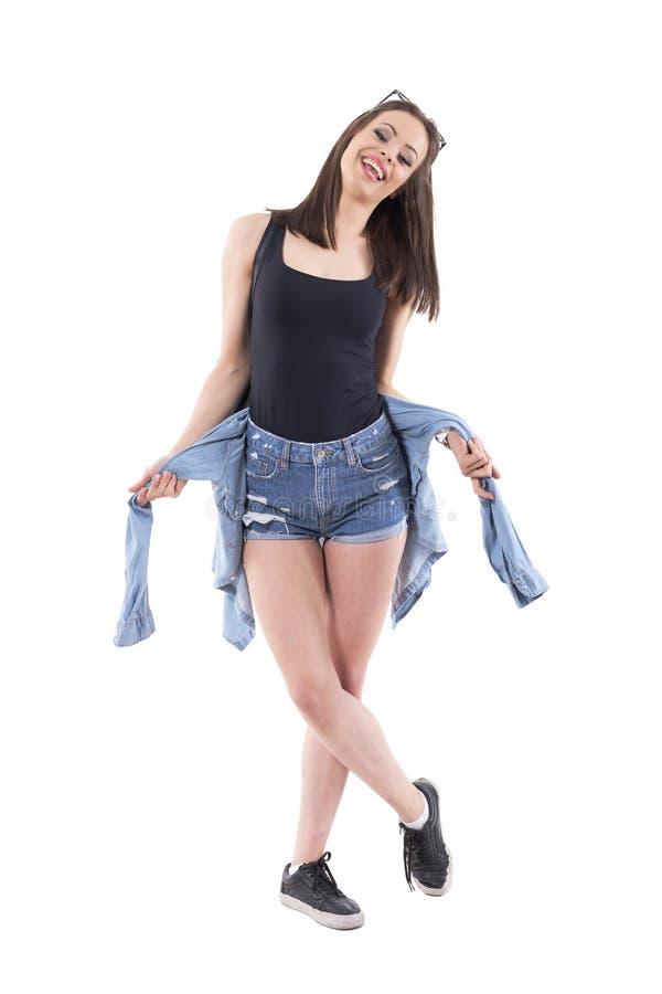 Счастливая молодая стильная женщина в шортах джинсов представляя и усмехаясь с курткой джинсовой ткани стоковое изображение