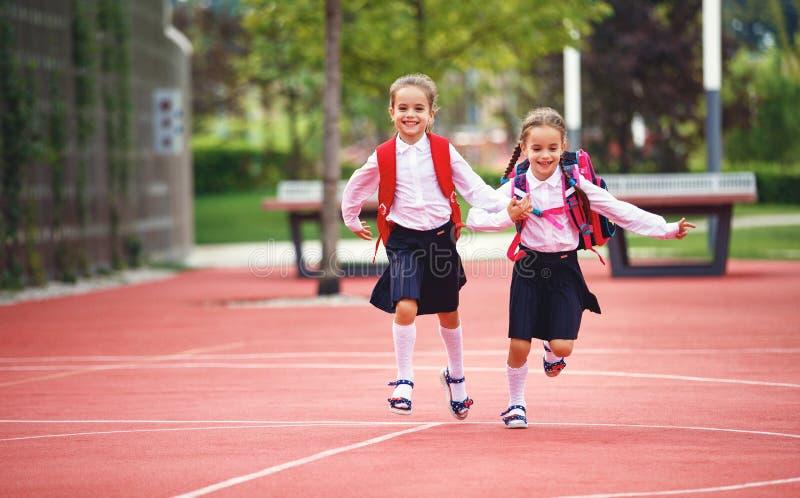 Счастливая начальная школа студента школьницы подруги детей стоковое фото