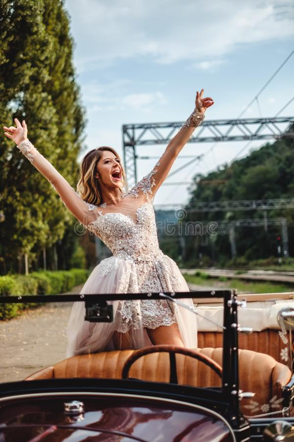 Счастливая невеста кричащая от классического автомобиля с откидным верхом стоковое фото