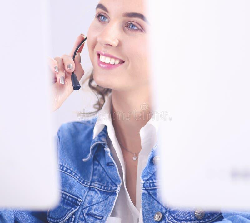 Счастливая очаровательная молодая женщина сидя и работая с ноутбуком используя шлемофон в офисе стоковые изображения rf