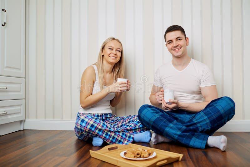 Счастливая пара в пижамах сидит на поле striped backgr стены стоковое изображение rf