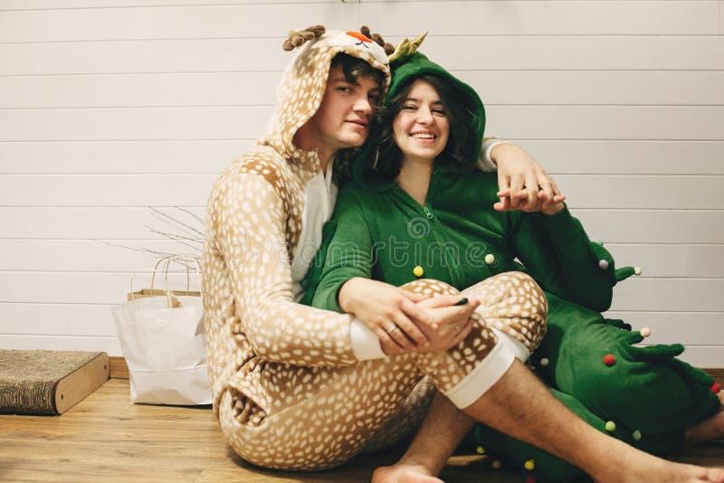 Счастливая пара в праздничных пижамах, веселиться на рождественских подарках, сидеть на полу Празднование Рождества или Нового го стоковое фото